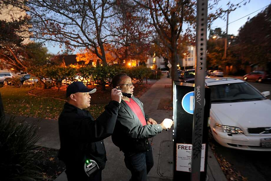 A parking control officer helps Robert Lacy purchase some parking time at a multi-space meter near Piedmont Avenue in Oakland. A new report from the city auditor says Oakland has never reimbursed people who mistakenly pay parking tickets twice, as is required by state law. Last year's overpayments added up to $316,000. Photo: Noah Berger, Special To The Chronicle