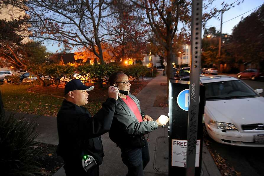 A parking control officer helps Robert Lacy purchase some parking time at a multi-space meter near P