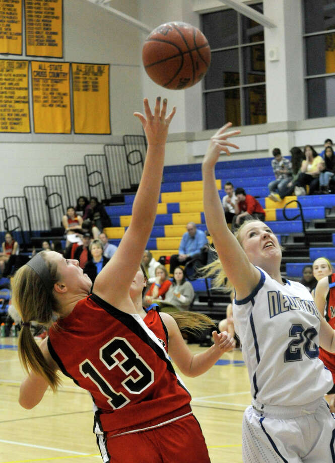Masuk's Paige Santee and Newtown's Kristiana Engler compete for the rebound during the Nighthawk's game against Masuk at Newtown High School on Wednesday, Dec. 19, 2012. Wednesday's basketball game was the first sporting event in Newtown since the Sandy Hook Elementary School shooting. Newtown won, 64-44. Photo: Jason Rearick / The News-Times
