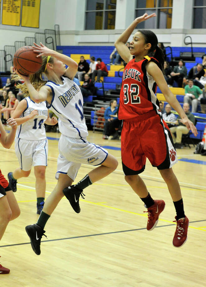 Newtown's Sarah Lynch attempts to shoot while under pressure from the leaping Thomese Holman, of Masuk, during the Nighthawk's game against Masuk at Newtown High School on Wednesday, Dec. 19, 2012. Wednesday's basketball game was the first sporting event in Newtown since the Sandy Hook Elementary School shooting. Newtown won, 64-44. Photo: Jason Rearick / The News-Times