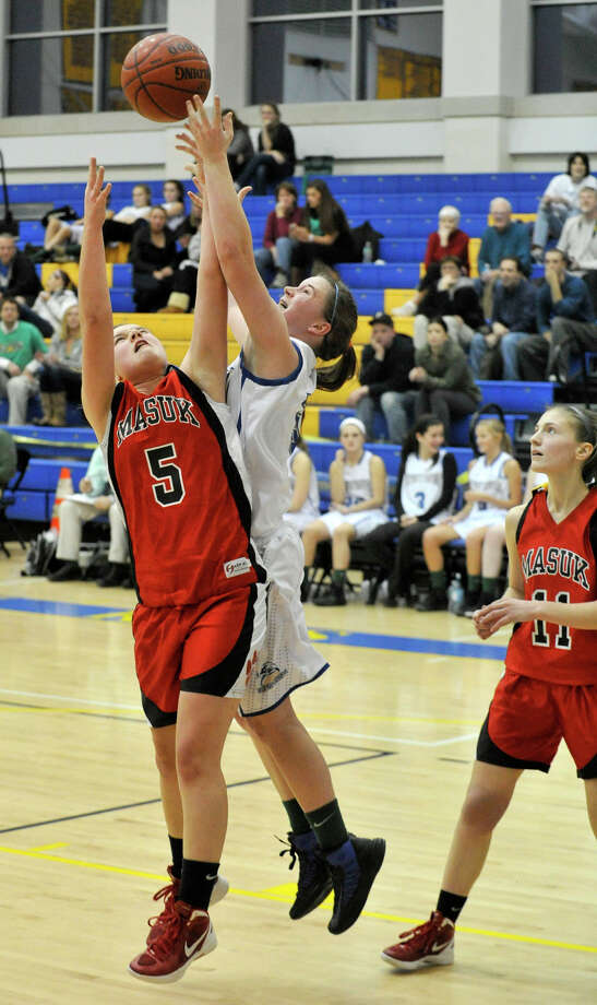 Masuk's Victoria Schiebe and Newtown's Cassie Ekstrom compete for the rebound during the Nighthawk's game against Masuk at Newtown High School on Wednesday, Dec. 19, 2012. Wednesday's basketball game was the first sporting event in Newtown since the Sandy Hook Elementary School shooting. Newtown won, 64-44. Photo: Jason Rearick / The News-Times