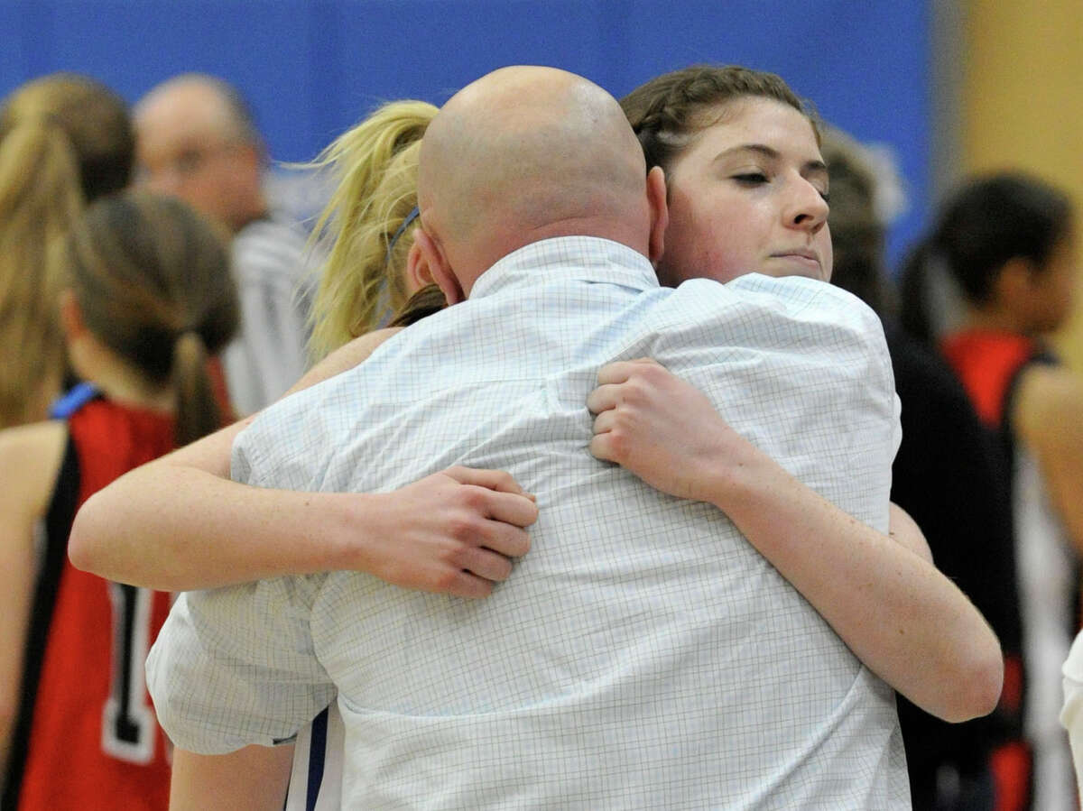 Newtown girls basketball head coach Jeremy O'Connell, back showing, hugs his team member Samantha Steimle after the Nighthawk's 64-44 win against Masuk at Newtown High School on Wednesday, Dec. 19, 2012. Wednesday's basketball game was the first sporting event in Newtown since the Sandy Hook Elementary School shooting.