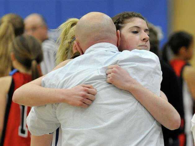 Newtown girls basketball head coach Jeremy O'Connell, back showing, hugs his team member Samantha Steimle after the Nighthawk's 64-44 win against Masuk at Newtown High School on Wednesday, Dec. 19, 2012. Wednesday's basketball game was the first sporting event in Newtown since the Sandy Hook Elementary School shooting. Photo: Jason Rearick / The News-Times