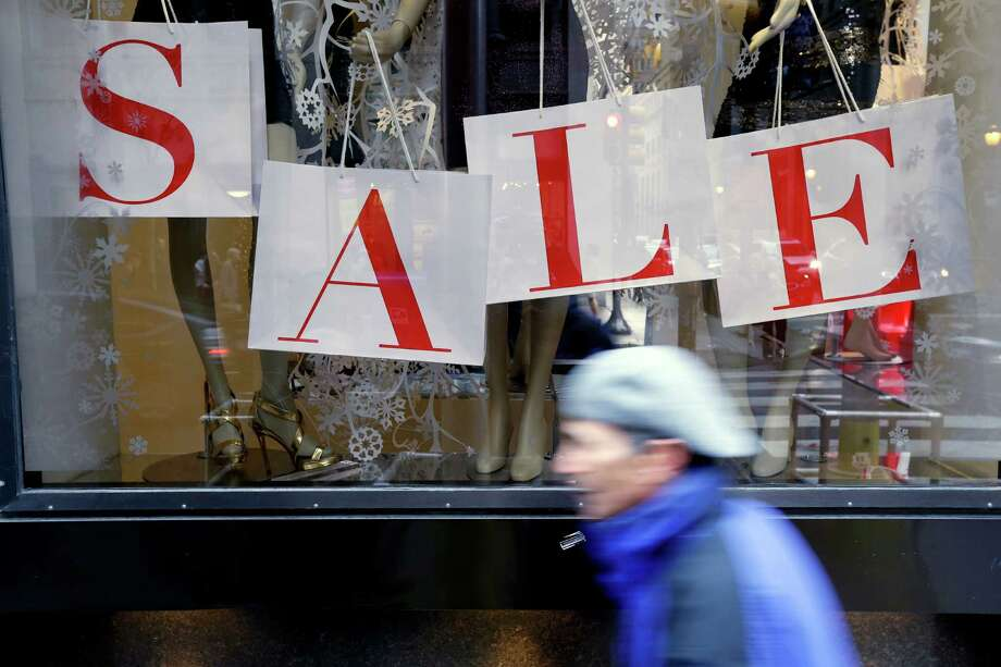 "In this Tuesday, Dec. 18, 2012, photo, a person passes a retail store with sale sign displayed in the window in Philadelphia. When it comes to big discounts, better late than never. This holiday shopping season, stores haven't been offering the same big discounts as they did in previous years as they tried to lure shoppers in with other incentives,but during the final days leading up to Christmas, shoppers will see more of those jaw-dropping ""70 percent off"" sale signs as stores try to salvage a season that so far has been disappointing.  (AP Photo/Matt Rourke) Photo: Matt Rourke"