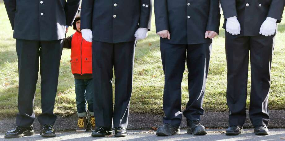 A child peers through firefighters standing during the funeral procession for school shooting victim Daniel Gerard Barden in Newtown, Conn., on Wednesday. Daniel said he wanted to be a firefighter when he grew up. Photo: Charles Krupa, STF / AP