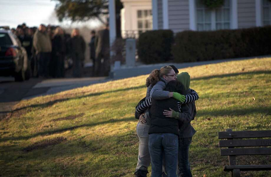 WOODBURY, CT - DECEMBER 19:  Mourners hug outside the wake of school principal Dawn Hochsprung, December 19, 2012 in Woodbury, Connecticut. Six victims of the Newtown school shooting are being honored at funerals and visitations across the state today for the victims of Sandy Hook Elementary School. (Photo by Allison Joyce/Getty Images) Photo: Allison Joyce