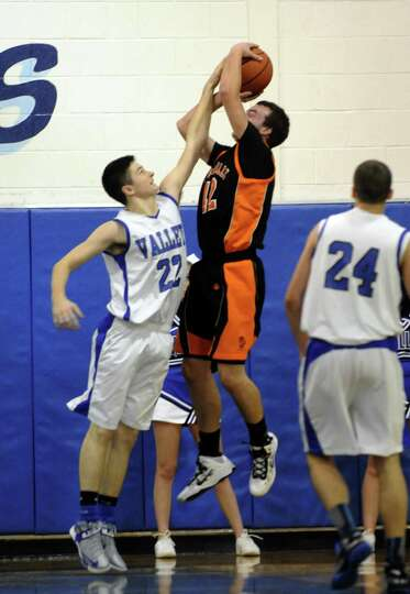 Hoosic Valley's John Rooney blocks a shot by Schuylerville's Ryan Buell during their boy's basketbal