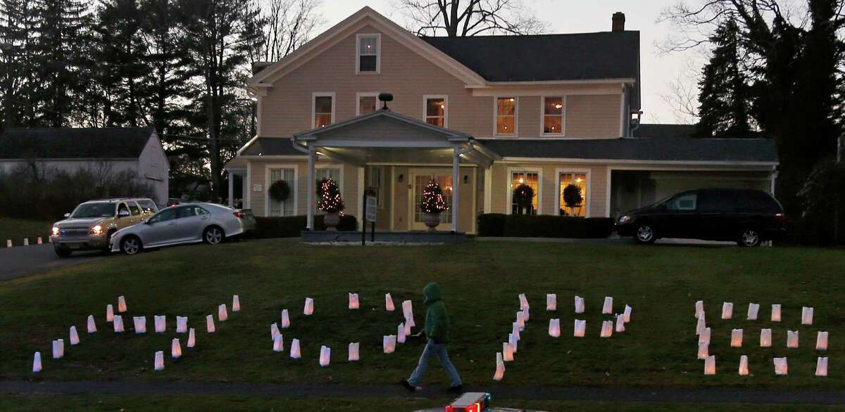 """The word """"HOPE"""" is illuminated on the front lawn of a funeral home hosting the wake of Sandy Hook Elementary School principal Dawn Lafferty Hochsprung in Woodbury, Conn., Wednesday, Dec. 19, 2012. Hochsprung was killed when Adam Lanza walked into Sandy Hook Elementary School in Newtown, Conn., Dec. 14, and opened fire, killing 26 people, including 20 children, before killing himself. (AP Photo/Charles Krupa)"""