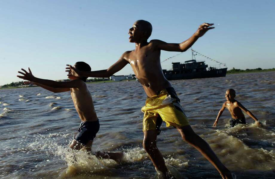 FILE - In this Oct. 14, 2012 file photo, children play in the water in Asuncion Bay, Paraguay. A poll released Wednesday of nearly 150,000 people around the world says seven of the world's 10 countries with the most upbeat attitudes are in Latin America. Gallup Inc. asked about 1,000 people in each of 148 countries last year if they were well-rested, had been treated with respect, smiled or laughed a lot, learned or did something interesting and felt feelings of enjoyment. In Panama and Paraguay, 85 percent of those polled said yes to all five, putting those countries at the top of the list. (AP Photo/Jorge Saenz, File) Photo: Jorge Saenz