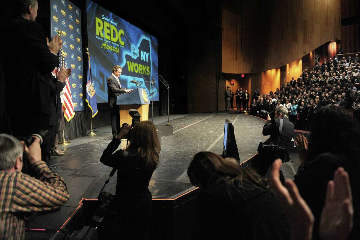 Governor Andrew Cuomo, background at podium, gets a standing ovation as he begins his address at the New York State Regional Economic Development Awards at the Hart Theatre at the Egg on Wednesday, Dec. 19, 2012 in Albany, NY. (Paul Buckowski / Times Union)