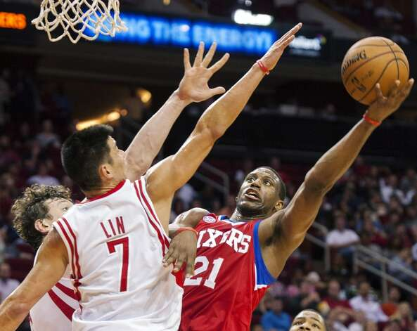Thaddeus Young of the 76ers attempts a shot over Jeremy Lin and Omer Asik of the Rockets. (Dave Einsel / Associated Press)