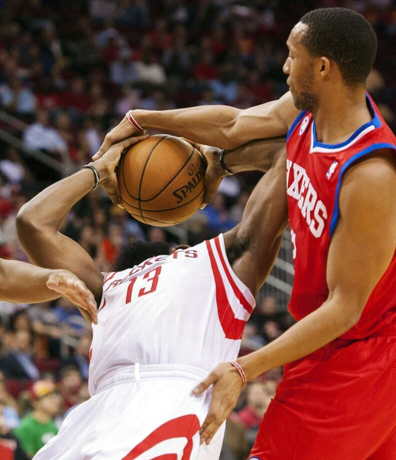 Evan Turner of the 76ers fouls Rockets guard James Harden. (Dave Einsel / Associated Press)