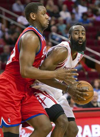 Lavoy Allen of the Philadelphia 76ers defends Rockets guard James Harden. (Dave Einsel / Associated Press)