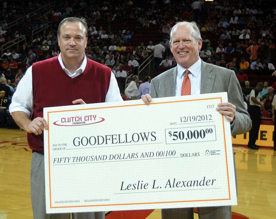 Rockets CEO Tad Brown, at left, presents a $50,000 check for Goodfellows to the Houston Chronicle' Chairman Jack Sweeney during a time-out of the Rockets game (Dave Rossman / For the Chronicle)