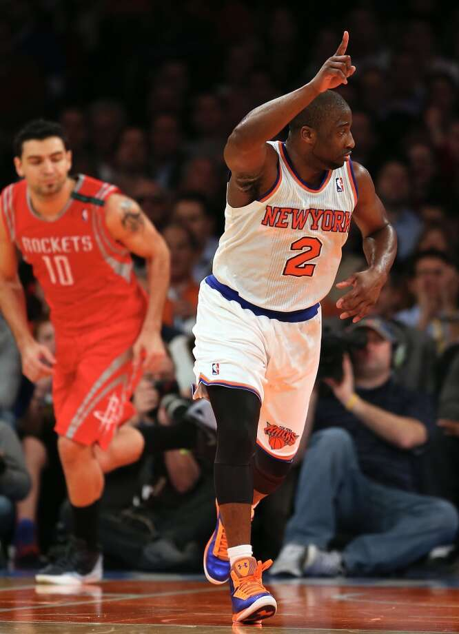 Knicks guard Raymond Felton celebrates his shot as Rockets forward Carlos Delfino runs up the court. (Getty Images)