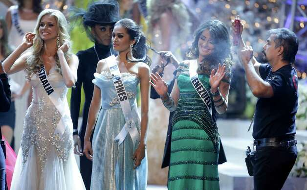 Miss Venezuela, Irene Sofia Esser Quintero, right, reacts as a hair stylist touches up her hair with hairspray while waiting during a commercial break with Miss Australia, left, Renae Ayris, and Miss Philippines Janine Tugonon. Photo: AP