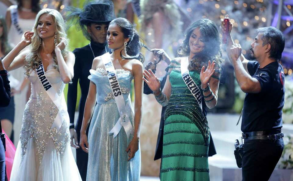 Miss Venezuela, Irene Sofia Esser Quintero, right, reacts as a hair stylist touches up her hair with