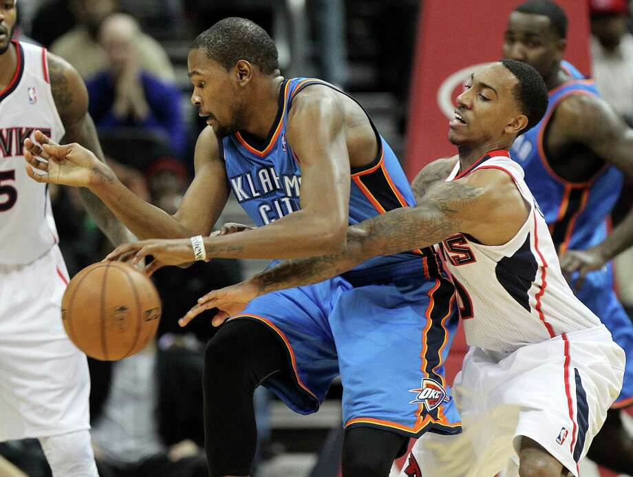 Kevin Durant shook off the defensive efforts of Jeff Teague, right, and other Hawks while scoring a season-high 41 points in the Thunder's 12th straight win. Photo: CURTIS COMPTON, MBR / Atlanta Journal-Constitution