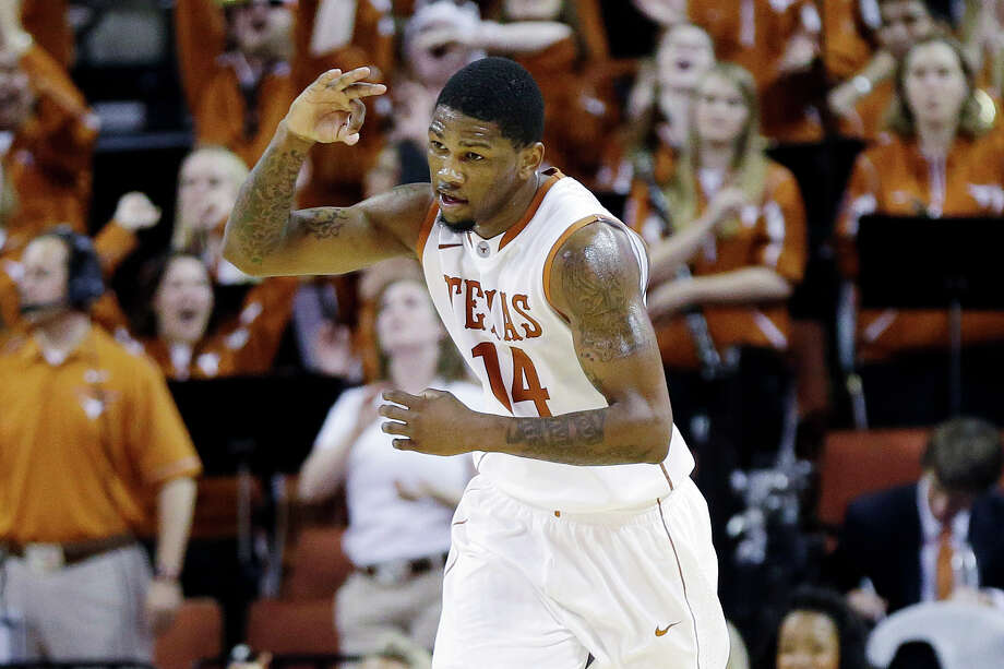Julien Lewis signals a 3-pointer after connecting on a night in which UT surpassed its season scoring high by 10 points. Photo: Eric Gay, STF / AP