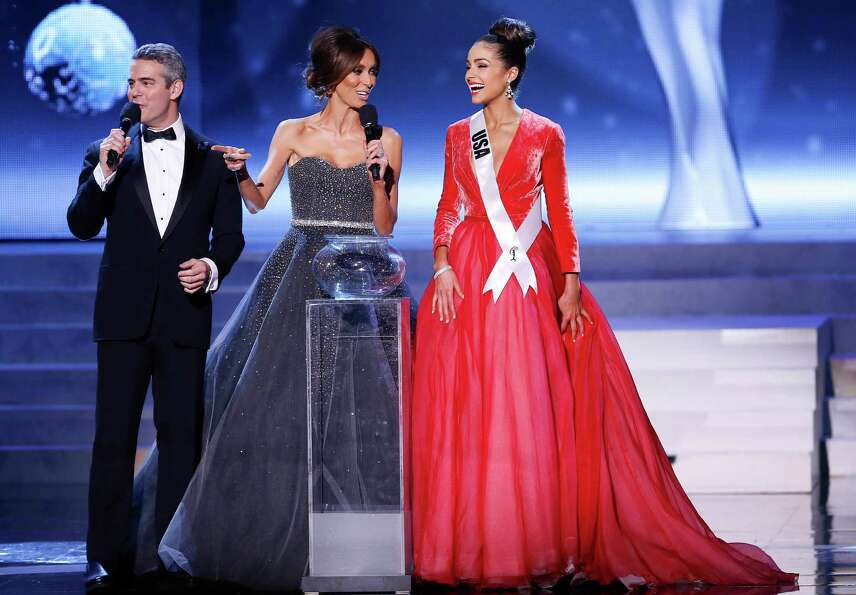 Miss Universe hosts Andy Cohen, left, and Giuliana Rancic, center, react as Miss USA, Olivia Culpo,