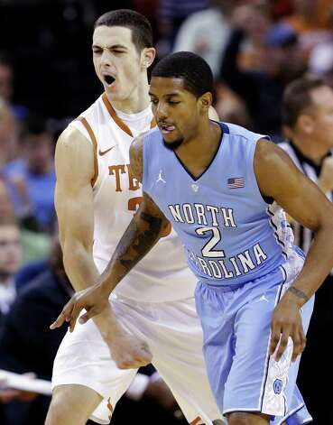 Texas' Ioannis Papapetrou, left, reacts next to North Carolina's Leslie McDonald (2) after scoring during the first half of an NCAA college basketball game, Wednesday, Dec. 19, 2012, in Austin, Texas. (AP Photo/Eric Gay) Photo: Eric Gay, Associated Press / AP