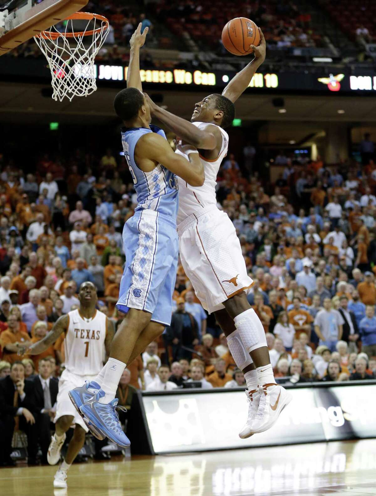 Texas' Jonathan Holmes, right, scores over North Carolina's J.P. Tokoto, left, during the second half of an NCAA college basketball game on Wednesday, Dec. 19, 2012, in Austin, Texas. Texas won 85-67. (AP Photo/Eric Gay)