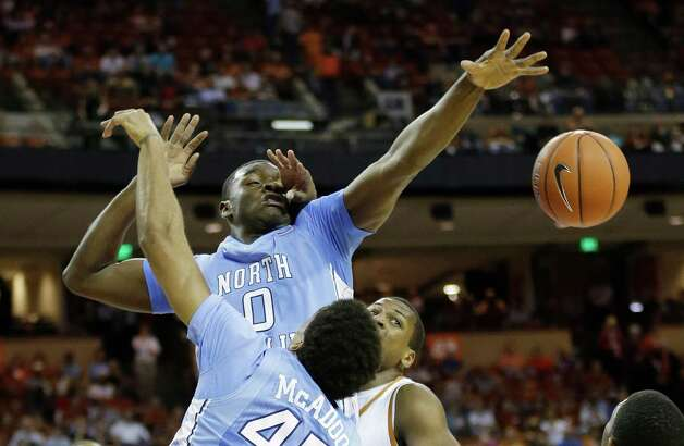 North Carolina's Joel James (0) is fouled by Texas' Jonathan Holmes, right, during the first half of an NCAA college basketball game on Wednesday, Dec. 19, 2012, in Austin, Texas. (AP Photo/Eric Gay) Photo: Eric Gay, Associated Press / AP