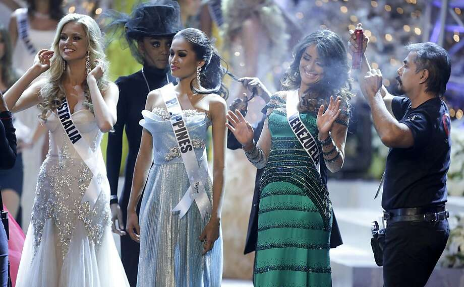 Miss Venezuela, Irene Sofia Esser Quintero, right, reacts as a hair stylist touches up her hair with hairspray while waiting during a commercial break with Miss Australia, left, Renae Ayris, and Miss Philippines Janine Tugonon, during the Miss Universe pageant, Wednesday, Dec. 19, 2012, in Las Vegas. (AP Photo/Julie Jacobson) Photo: Julie Jacobson, Associated Press