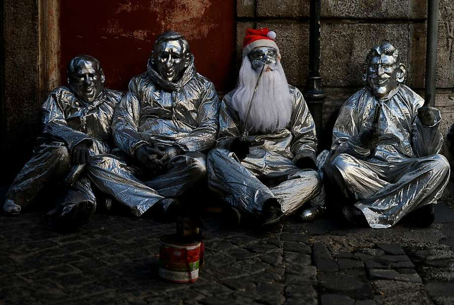 A group of street beggers dressed as metal statues sit in downtown Rome on December 19, 2012.    AFP PHOTO/ Filippo MONTEFORTEFILIPPO MONTEFORTE/AFP/Getty Images Photo: Filippo Monteforte, AFP/Getty Images