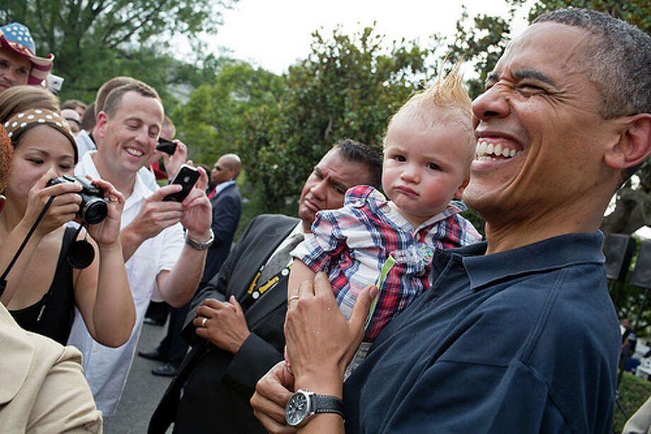 President Barack Obama holds a baby while greeting guests during an Independence Day celebration on the South Lawn of the White House, July 4, 2012. (Pete Souza / The White House)