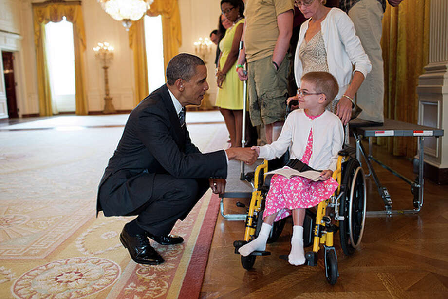 President Barack Obama greets Holli Benson during a visit with wounded warriors in the East Room of the White House, Aug. 23, 2012. Benson accompanied her brother, SSG Michael Benson, during a tour of the White House.  (Pete Souza / The White House)