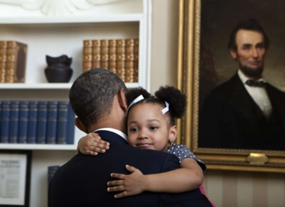 President Barack Obama holds Arianna Holmes, 3, before taking a departure photo with members of her family in the Oval Office, Feb. 1, 2012.  (Lawrence Jackson / The White House)