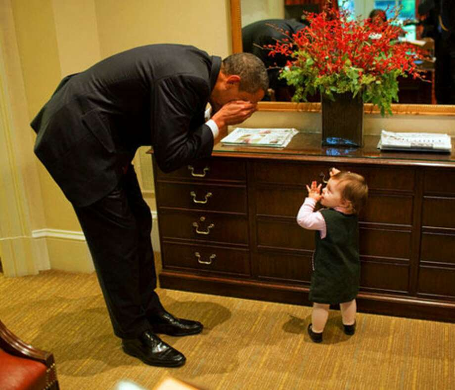 President Barack Obama plays peek-a-boo with Maeve Beliveau, the daughter of Director of Advance Emmett Beliveau, in the Outer Oval Office, Oct. 30, 2009. (Pete Souza / The White House)