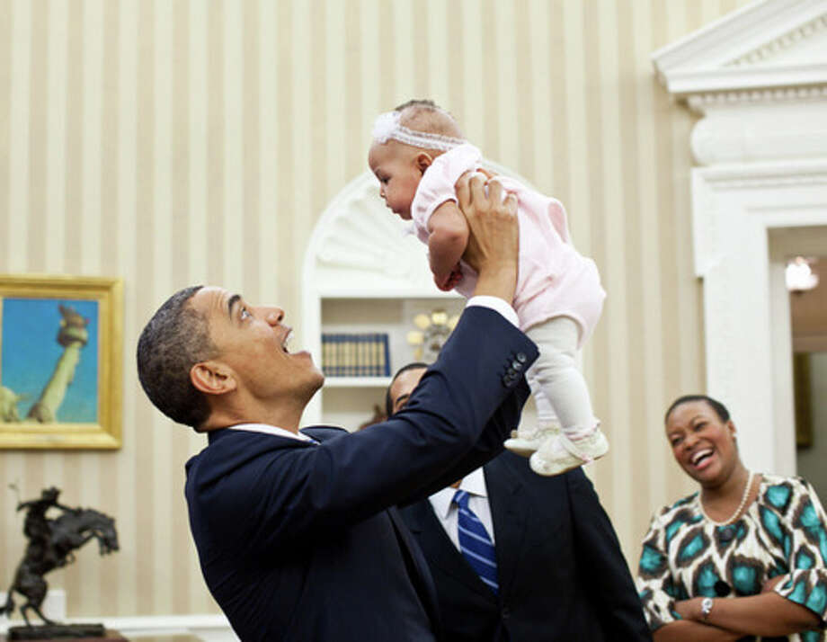President Barack Obama holds up four-month-old Alia Jawando as her father, William Jawando, Deputy Associate Director of Public Engagement, and her mother Michele look on in the Oval Office, March 9, 2011. (Pete Souza / The White House)