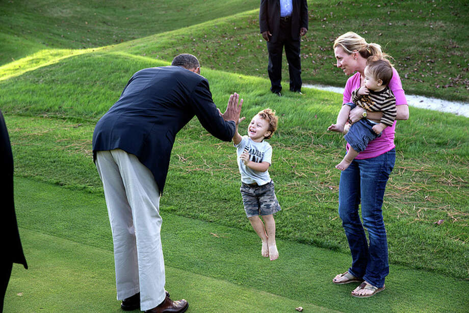 President Barack Obama greets a child on the Kingsmill Resort grounds during a break from debate prep in Williamsburg, Va., Oct. 14, 2012.  (Pete Souza / White House)