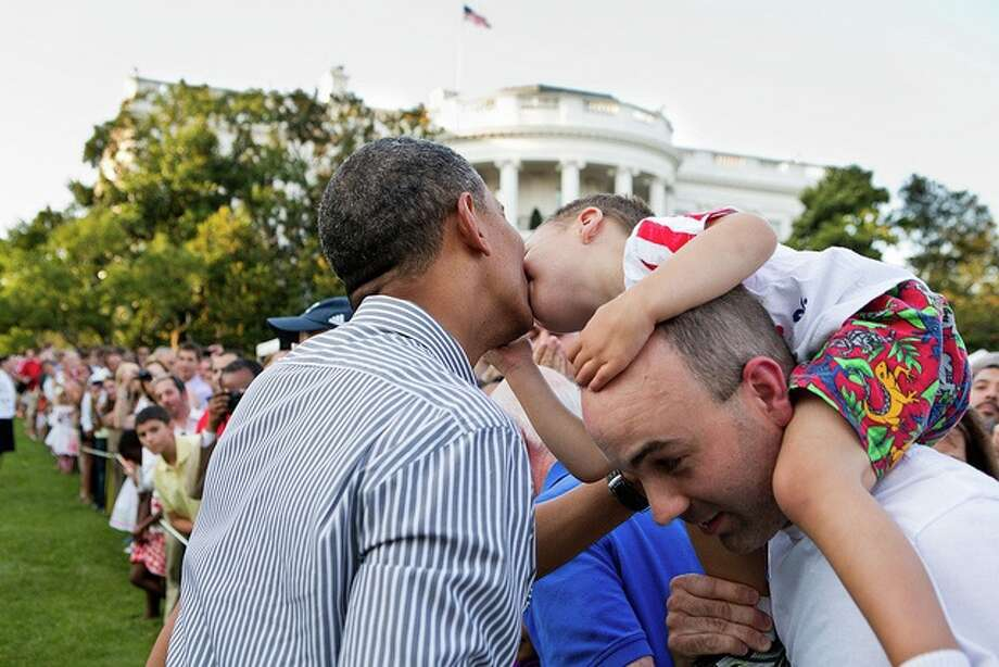 A little boy leans over to kiss President Barack Obama during the Congressional picnic on the South Lawn of the White House, June 27, 2012. (Pete Souza / White House)