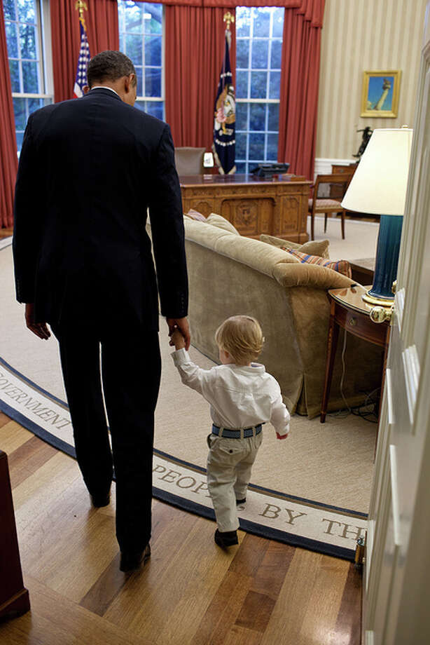 When a White House staff member leaves their job, the President usually invites the staff member and his family to the Oval Office for a family photo to thank them for their service. Here the President walks with William Jones, son of departing aide Luke Jones, before a family photo. (Pete Souza / The White House)
