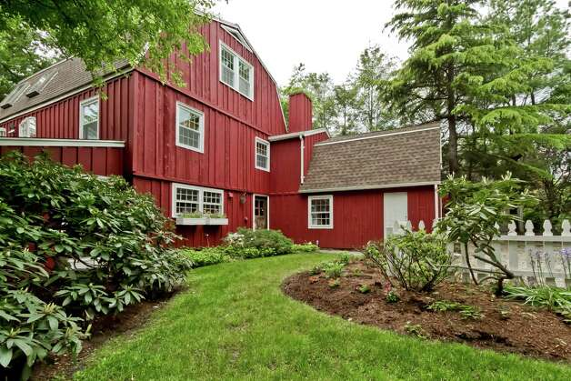 This antique converted red barn at 1 Valley Field Road, built in 1920, has 3,300 square feet of living space in an unusual configuration that has a two-story living room with vaulted ceiling and over-sized stone fireplace on the second floor. Photo: Contributed Photo/Rob Staub / WWW.RobStaubphoto.com