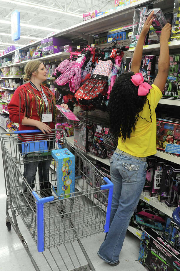Alex Martin watches as Ashanti Jones, reaches for a toy at Walmart during a $50 shopping spree on Wednesday. Jones was one of several Beaumont students who received a gift card from a donation by a Houston attorney. Photo taken Wednesday, December 19, 2012 Guiseppe Barranco/The Enterprise Photo: Guiseppe Barranco, STAFF PHOTOGRAPHER / The Beaumont Enterprise