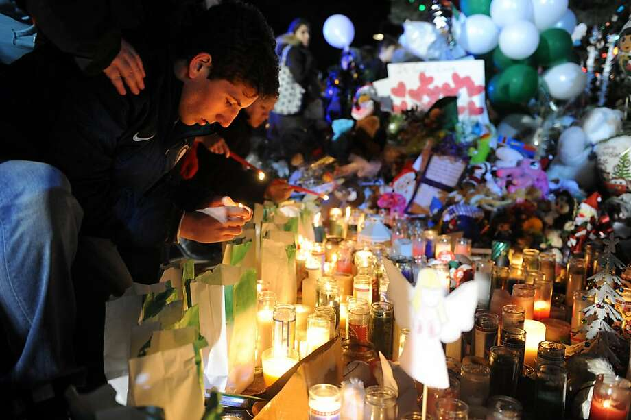 Mourners light candles and say prayers at a memorial for shooting victims near Sandy Hook Elementary School Wednesday, Dec. 19, 2012 in Newtown, Conn. Photo: Autumn Driscoll