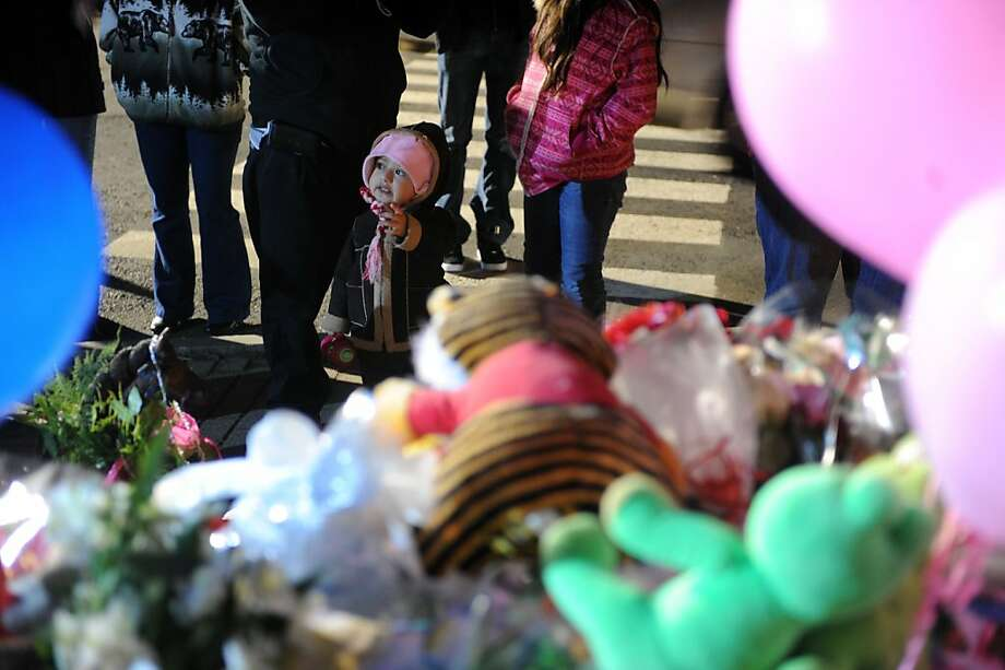 A toddler stands with her parents as they say a prayer at a memorial for shooting victims near Sandy Hook Elementary School Wednesday, Dec. 19, 2012 in Newtown, Conn. Photo: Autumn Driscoll