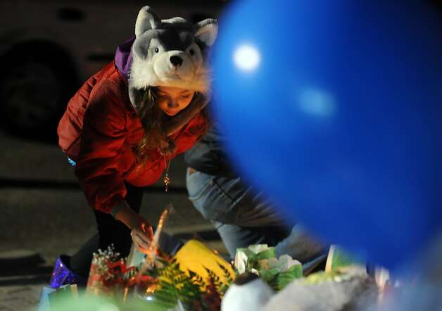Ten-year-old Fijare Plous, of Higganum, lights a candle at a memorial for shooting victims near Sandy Hook Elementary School Wednesday, Dec. 19, 2012 in Newtown, Conn.  The Plous family was on their way to visit relatives out of state and wanted to stop in Newtown to pay their respects to the victims of last week's mass shooting. Photo: Autumn Driscoll
