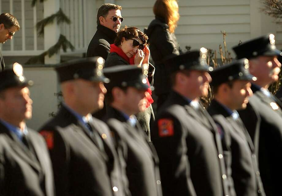 A bystander wipes a tear as firefighters stand at attention outside the funeral for Daniel Barden, one of the twenty children killed in the Sandy Hook Elementary School shooting, at St. Rose of Lima Catholic Church in Newtown on Wednesday, December 19, 2012. Photo: Brian A. Pounds