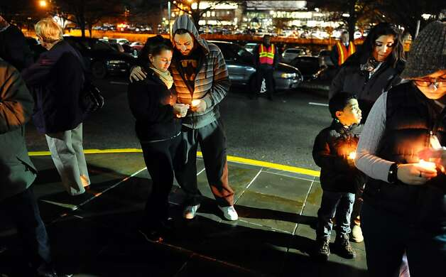 Emily LaMotta and John Perez, center, take part in a candlelight vigil held to remember the Newtown massacre victims at Norwalk Community College in Norwalk, Conn. on Tuesday December 18, 2012. Photo: Christian Abraham