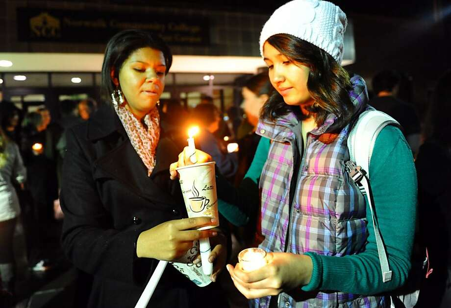 Students Deanna Fields, left, and Aygul Gara-Dashly take part in a candlelight vigil held to remember the Newtown massacre victims at Norwalk Community College in Norwalk, Conn. on Tuesday December 18, 2012. Photo: Christian Abraham