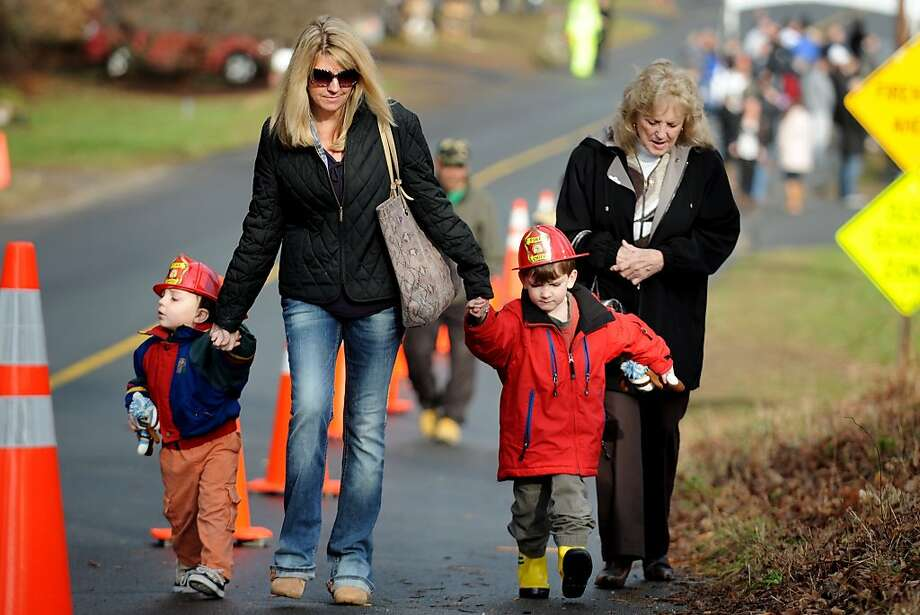 Zachary, 2, and Nathan, 4, Johnston, of Easton, wear the new fire helmets they received from firefighters at Sandy Hook Volunteer Fire Department, in Newtown, Conn. Dec. 18th, 2012. The boys, seen here with their mother, Joelle Johnston, and neighbor Carolette Johnson, visited the Sandy Hook firehouse Tuesday to delivers a gift to first responders. Photo: Ned Gerard