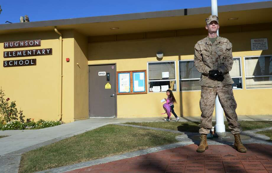 U.S Marine Corps Reserve Sgt. Craig Pusley stands guard as kindergarten student Liset Corona, 5, walks to her class at Hughson Elementary School on Wednesday morning Dec. 19, 2012 in Hughson, Calif. Pusley plans to stand guard here during the start and end of the school day for 30 days. He says he plans to have his son Canon, 3, attend the school next year.  (AP Photo/The Modesto Bee, Ed Crisostomo) LOCAL TV OUT (KXTV10, KCRA3, KOVR13, FOX40, KMAX31, KQCA58, CENTRAL VALLEY TV); LOCAL PRINT OUT (TURLOCK JOURNAL, CERES COURIER, OAKDALE LEADER, MODESTO VIEW, PATTERSON IRRIGATOR, MANTECA BULLETIN, RIPON, RECROD, SONORA UNION DEMOCRAT, AMADOR LEDGER DISPATCH, ESCALON TIMES, CALAVERAS ENTERPRISE, RIVERBANKS NEWS) LOCAL INTERNET OUT (TURLOCK CITY NEWS.COM, MOTHER LODE.COM) Photo: Ed Crisostomo, MBR / The Modesto Bee