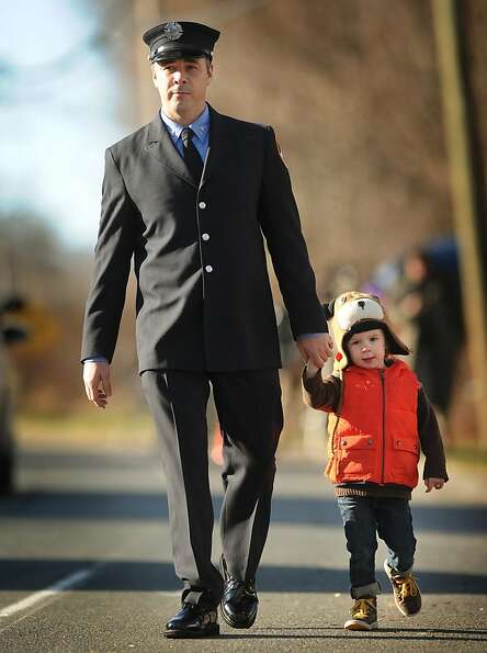 An FDNY firefighter and his son exit the funeral of Daniel Barden, one of the twenty children killed