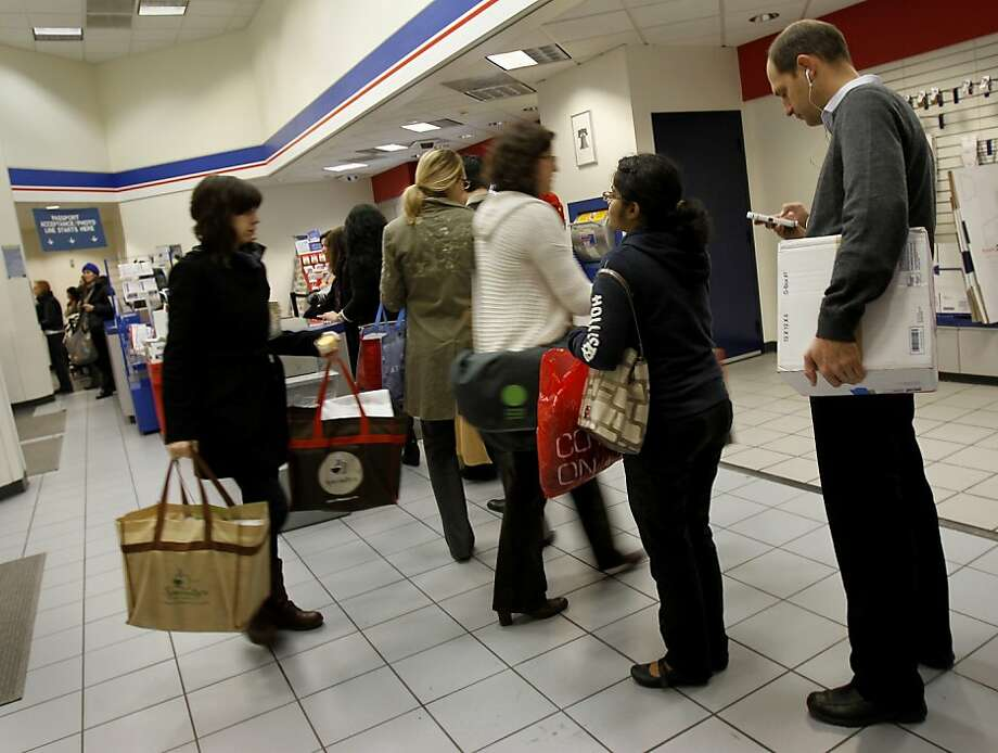 People wait in line last year at the Sutter Street post office, above. Mail carrier Juan Padilla makes a delivery, below. The postal service operates at a deficit. Photo: Brant Ward, The Chronicle