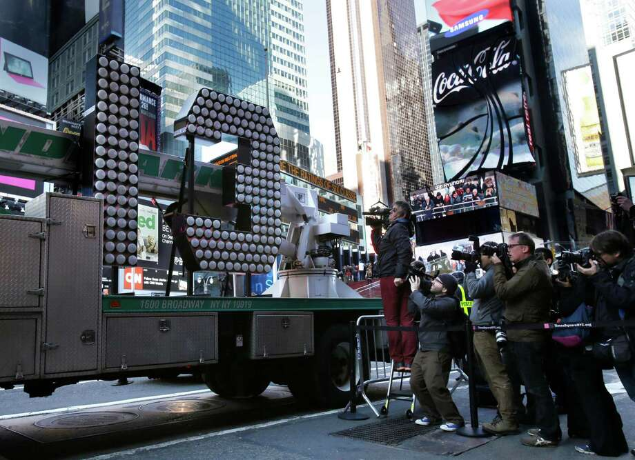 "Members of the media as the number ""13"" to be used during the New Year's Eve celebration in Times Square arrives to Times Square in New York, Wednesday, Dec. 19, 2012. Photo: Seth Wenig, AP / AP"